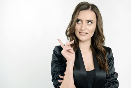 Young thoughtful business lady in black seems to have a brilliant idea isolated white background