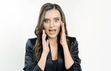 Real surprise emotions shown by a young cute woman in black official clothes isolated white background