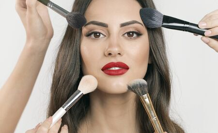 Chic young model having her makeup as multiple makeup brushes are used simultaneously isolated white background Archivio Fotografico
