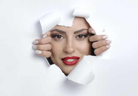 Conceptual photo of cute young womans smiling face with makeup looking through a hole in paper-like material wall