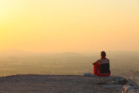 Lady sitzt bei Sonnenuntergang in Hampi, Indien