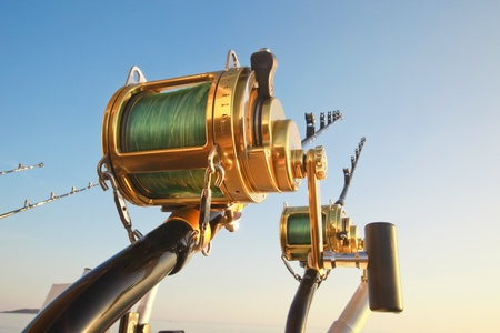 tackle: big game fishin reels and rods lit by setting sun