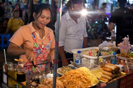 BANGKOK - JANUARY 12. Woman cooking on Khao San Road on January 12, 2012 in Bangkok, Thailand. Street cooking is a tradition and ubiquitous in Thailand.