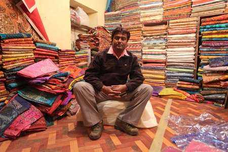 JAISALMER DECEMBER 2010 : Indian man posing in his textile shop in center of Jaisalmer, India on December 10. 2010. Price of cotton has increased due to floods.