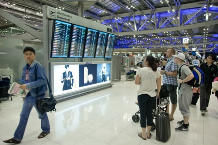 BANGKOK Ð JANUARY 17. People in front of departures board of Bangkok airport on January 17, 2012. early morning. Suvarnabhumi airport is world