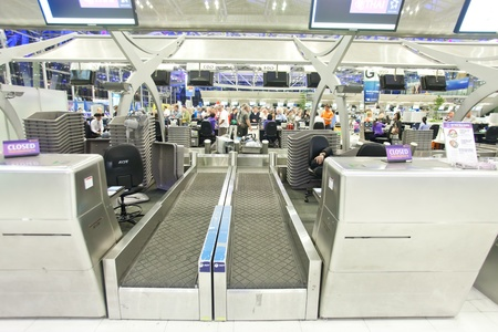 BANGKOK � JANUARY 17. Empty check-in counter with crowds in background in Bangkok airport on January 17, 2012. Suvarnabhumi airport is world