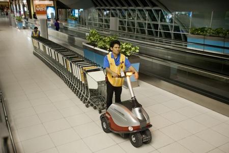 BANGKOK � JANUARY 17. Airport staff moving trolleys in early morning Bangkok airport on January 17, 2012. Suvarnabhumi airport is world