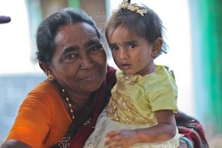 HAMPI – JANUARY 15 : Grandmother caring for grandchild in Hampi, India on January 15, 2011. In India It