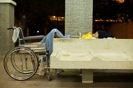 BANGKOK � JANUARY 13 : Homeless disabled man sleeping on a public concrete bench under brigde in downtown Bangkok on January 13, 2012. Downtown was spared of flooding in recent  disastrous floods in Thailand.