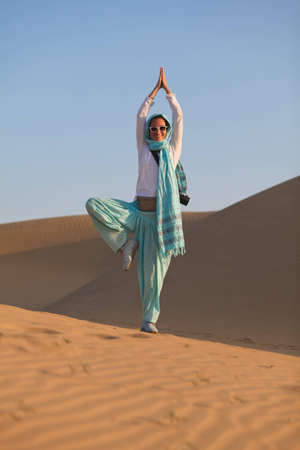 Woman doing Yoga tree pose in desert dunes photo