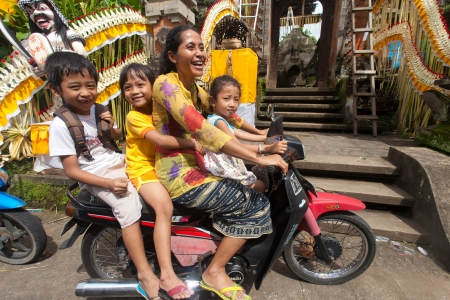 BALI - JANUARY 20. Woman driving her kids to school motorcycle on January 20, 2012 in Bali, Indonesia. Common Balinese cannot afford cars to transport their family.