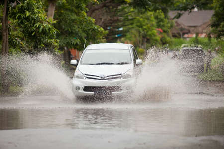 downpour: LAKE BATUR, BALI - JANUARY 21. Car driving through flooded street after downpour on Lake Batur on January 21, 2012 in Bali, Indonesia. Weather patterns have changed in recent years. Editorial