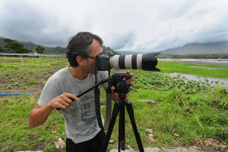 photojournalist: LAKE BATUR, BALI - JANUARY 21. Photojournalist Ognjen Maravic documenting life on Lake Batur on January 21, 2012 in Bali, Indonesia. Changing cultures due to tourism is one main topic worked on. Editorial