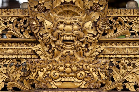 Balinese wooden sculpture of mask dragon face with golden paint