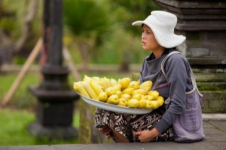 BALI - 22. Januar. Balinesische Frau verkauft Mais für die Pilger auf Mutter-Tempel in Besakih am 22. Januar 2012 in Bali, Indonesien. Es ist üblich, Erfrischungen und Speisen von Straßenhändlern in Besakih kaufen