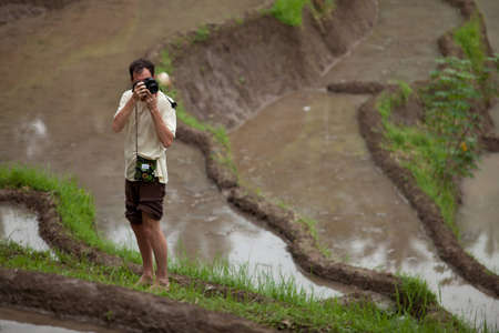 Photographer shooting locals in the paddy fields in Bali, Indonesia.