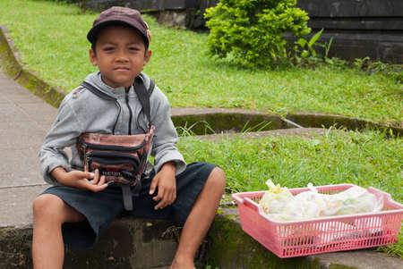 BALI - 22. Januar. Junge balinesischen verkauft Angebot für die Pilger auf Mutter-Tempel in Besakih in Bali am 22. Januar 2012 in Bali, Indonesien. Alle Familienmitglieder, jung und alt, zu beteiligen ist Geschäft. Editorial