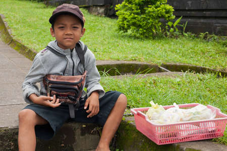 BALI - JANUARY 22. Young Balinese selling offerings to pilgrims at Mother Temple in Besakih in Bali on January 22, 2012 in Bali, Indonesia. All family members, young and old, participate is business.