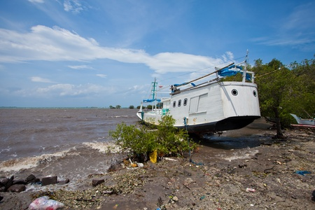 BALI - JANUARY 26. Boat washed up on shore of storm on January 26, 2012 in Bali, Indonesia. Material damage and six people lost their lives in windy storms.