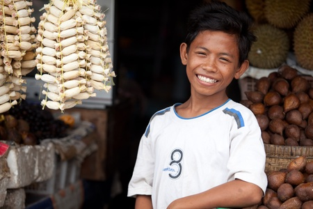 BALI - 26. Januar. Sohn eines balinesischen Obststand Besitzer charmante seine Kunden am 26. Januar 2012 in Bali, Indonesien. Alle Familienmitglieder teilnehmen Tagesgeschäft über die Runden kommen. Editorial