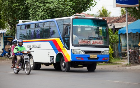 BALI - JANUARY 26. Bus and motorbike on the Gilimanuk route on January 26, 2012 in Bali, Indonesia. The Gilimanuk road is the busiest as it's the only connection with neighbouring island Java. Redakční