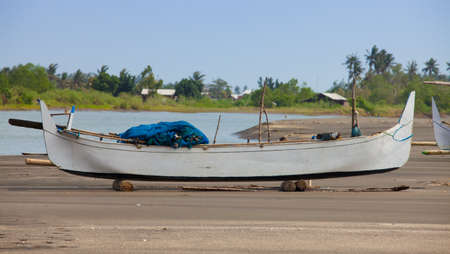 beached: Balinese wooden fishing boat beached on sand with blue fishing nets