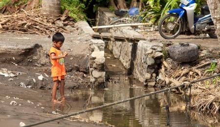 BALI - 26. Januar. Balinese Kind spielt in schmutziges Wasser am 26. Januar 2012 in Bali, Indonesien. Laut Asian Development Bank, über 100 Millionen Menschen in Indonesien keinen Zugang zu sauberem Wasser.