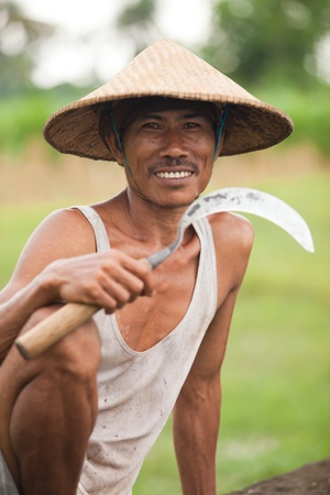 BALI - JANUARY 29  Portrait of traditional rice farmer with sickle on January 29, 2012 in Bali, Indonesia  Indonesia is currently the world
