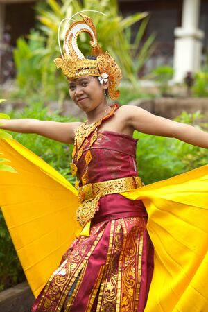 Young Balinese female dancer performing traditional Legong dance photo