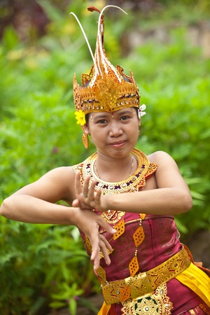 folk: Young Balinese female dancer performing traditional Legong dance