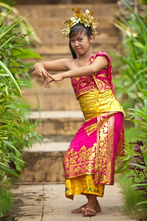 Young Balinese female dancer performing traditional Legong dance
