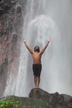 Man at waterfall raising his hands in feeling closer to nature photo