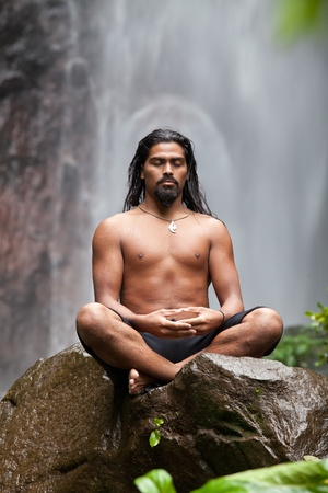 indian yoga: Man sitting in meditation on rock at waterfall in tropical rainforest Stock Photo