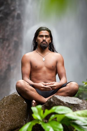 Man sitting in meditation on rock at waterfall in tropical rainforest photo