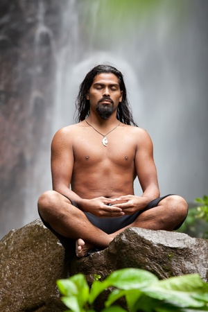 Man sitting in meditation on rock at waterfall in tropical rainforest Stock Photo