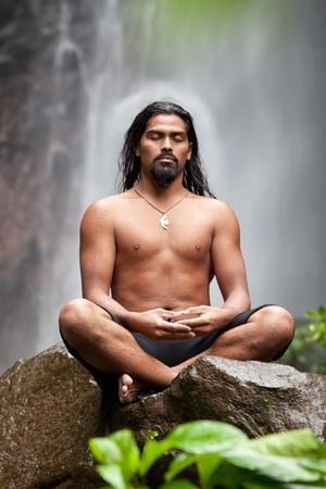 Man sitzt in der Meditation auf Felsen am Wasserfall im tropischen Regenwald