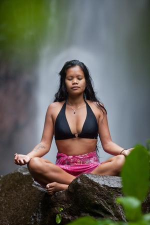Woman sitting in meditation on rock at waterfall in tropical rainforest photo