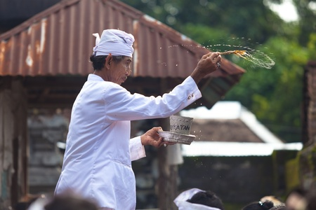 BALI - FEBRUARY 1. Priest blessing worshippers with holy water for Galungan ceremony on February 1, 2012 in Bali, Indonesia. Galungan's a Balinese holiday occuring every 210 days lasting 10 days. Stock Photo - 13336625