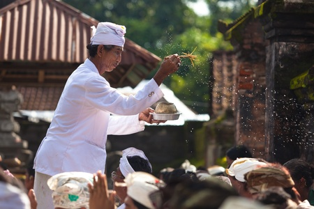 BALI - FEBRUARY 1. Priest blessing worshippers with holy water for Galungan ceremony on February 1, 2012 in Bali, Indonesia. Galungan's a Balinese holiday occuring every 210 days lasting 10 days. Stock Photo - 13336636