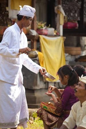 BALI - 1. Februar. Priest Segen Gläubigen mit Weihwasser für Galungan Preisverleihung am 1. Februar 2012 in Bali, Indonesien. Galungan ist ein balinesischer Urlaub vorkommenden alle 210 Tage dauert 10 Tage.