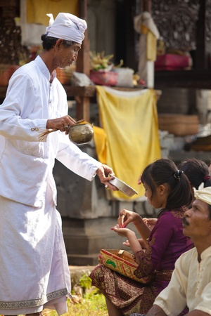 lasting: BALI - FEBRUARY 1. Priest blessing worshippers with holy water for Galungan ceremony on February 1, 2012 in Bali, Indonesia. Galungans a Balinese holiday occuring every 210 days lasting 10 days.