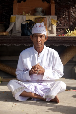 BALI - FEBRUARY 1. Hindu priest praying in local temple for Galungan ceremony on February 1, 2012 in Bali, Indonesia. Galungan's a Balinese holiday occuring every 210 days lasting 10 days. Stock Photo - 13336645
