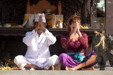 BALI - FEBRUARY 1. Priest praying with worshipper in temple for Galungan ceremony on February 1, 2012 in Bali, Indonesia. Galungans a Balinese holiday occuring every 210 days lasting 10 days.