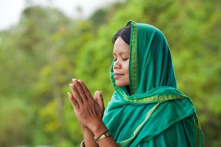 woman praying: Young south-east asian woman praying with head dress Stock Photo