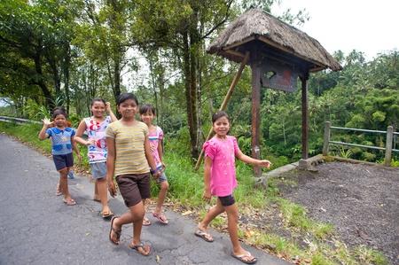Bank Światowy: BALI - 02 lutego. Młode dziewczyny balijskie chodzenie na wiejskiej drodze w dniu 2 lutego 2012 na wyspie Bali, Indonezja. 27% ludności kraju, jest młodszy niż 15 lat, zgodnie z Banku Światowego.