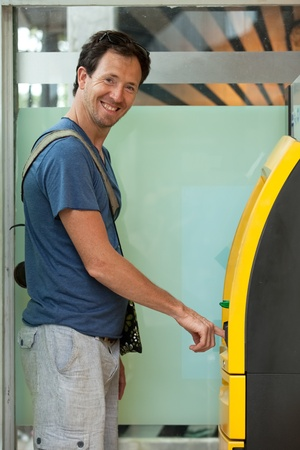 Young caucasian man withdrawing money at ATM Stock Photo - 13451941
