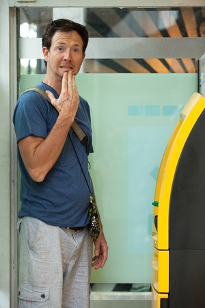 pincode: Young caucasian man withdrawing money at ATM Stock Photo