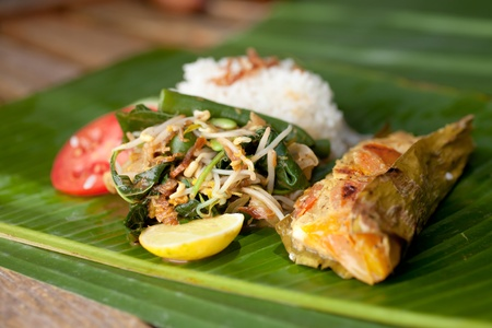 Special indonesian fish dish, Pepes Ikan, served on banana leaf photo