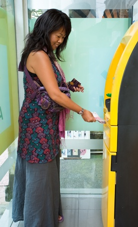 Asian woman withdrawing money at ATM photo