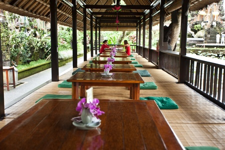 Cafe with low tables and green cushions with orchids on tables